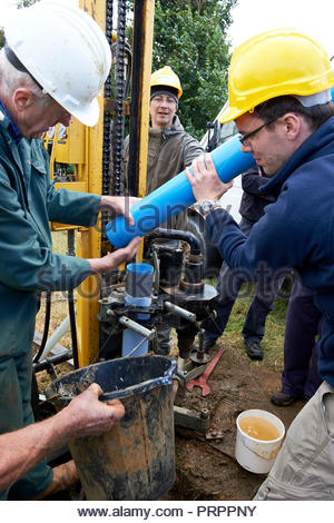 International students and a Drilling Engineer install slotted PVC water well casing with geo-textile membrane using a PAT-Drill 301 Rotary Drill Rig. - Stock Photo