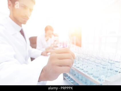 Beautiful medical doctors are working with test tubes and microscope at the lab - Stock Photo