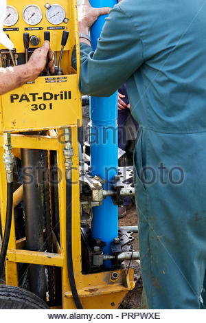 International students and Drilling Engineer install slotted PVC water well casing with geo-textile membrane using a PAT-Drill 301 Rotary Drill Rig. - Stock Photo
