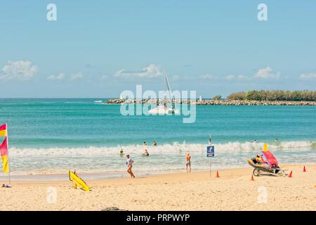 People enjoying a warm sunny day on the beach in Mooloolaba, one of Queensland's premier holiday destinations. - Stock Photo