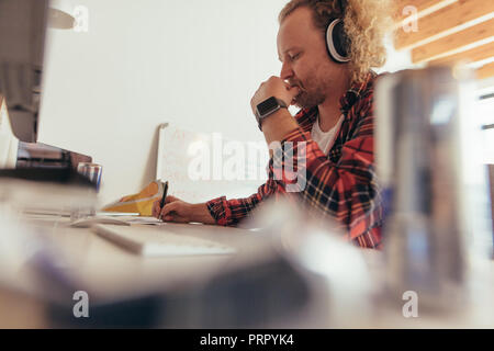 Man making some notes in copybook, sitting at small office table. Experience tech professional coding on a notepad in office. - Stock Photo