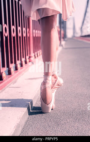 Beautiful nice ballerina wearing her pointe shoes - Stock Photo