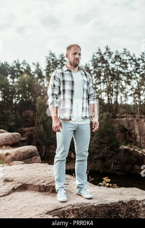 Handsome stylish man enjoying his weekend while spending it in natural environment - Stock Photo
