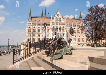 Budapest, Hungary - June 4, 2017: Sitting sculptural portrait of hungarian poet Attila Jozsef placed on the stairs near Hungarian parliament and Danub - Stock Photo