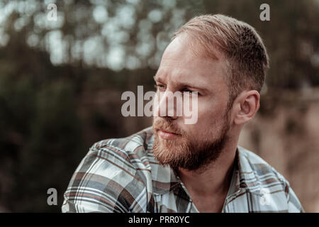 Close up of handsome bearded blonde-haired man feeling rather serious