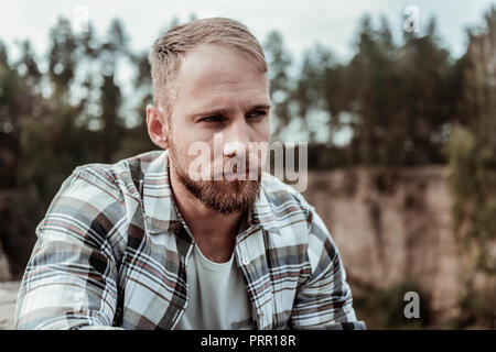 Good-looking dark-eyed man wearing squared shirt sitting outside enjoying fresh air - Stock Photo