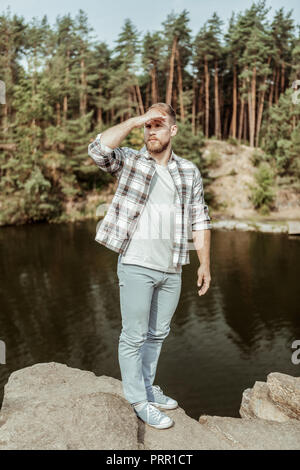 Young and free traveler feeling amazing standing on the rock near big beautiful river - Stock Photo