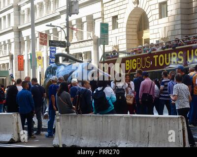Tourists crowded around the Wall Street Charging Bull while others peer down from an open top tour bus on Broadway, New York, NY, USA. - Stock Photo