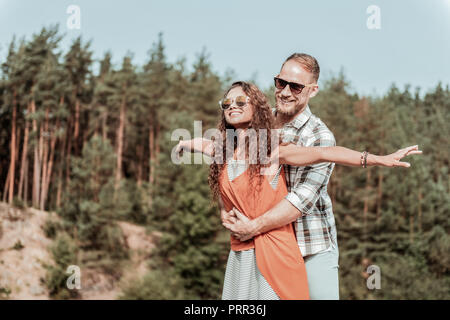 Beaming happy loving couple enjoying their secret hideaway in the forest - Stock Photo