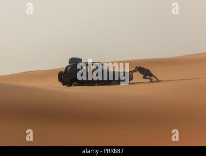 Man pushing a broken down car in the namib desert, Namibe Province, Iona National Park, Angola - Stock Photo