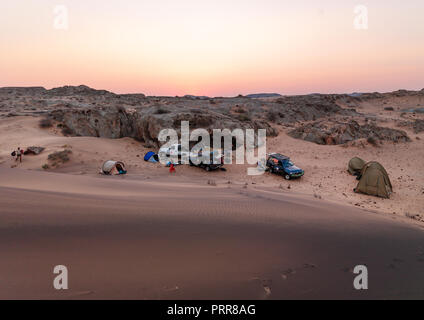 Tourists camping in the pink sands, Namibe Province, Iona National Park, Angola - Stock Photo