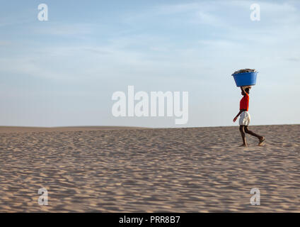 Angolan woman carrying fishes on her head along the beach, Namibe Province, Tombua, Angola - Stock Photo