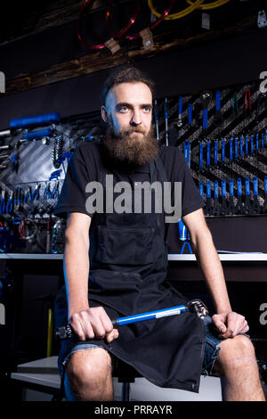Portrait of small business owner of young man with beard. Guy bicycle mechanic workshop worker sitting with tool in his hand in a working black clothe - Stock Photo