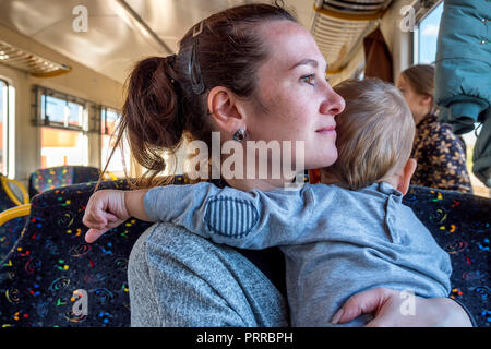 Young happy mother holding baby while he pulls her hair while travelling by train - Stock Photo