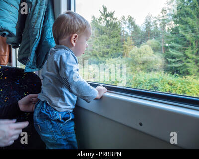 Beautiful toddler boy looking out train window outside, while it moving. Going on vacations and traveling by railway in winter - Stock Photo