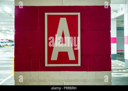 letter A pink sign on brick column in shopping centre car park - Stock Photo