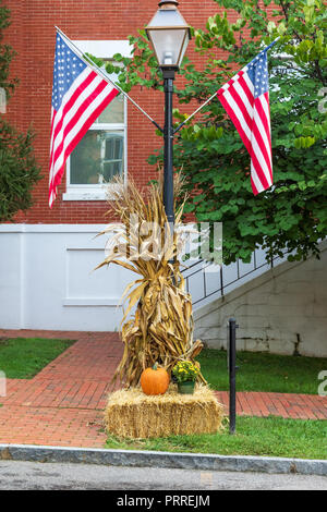 JONESBOROUGH, TN, USA-Two American flags mounted on a street light decorated for Thanksgiving. - Stock Photo
