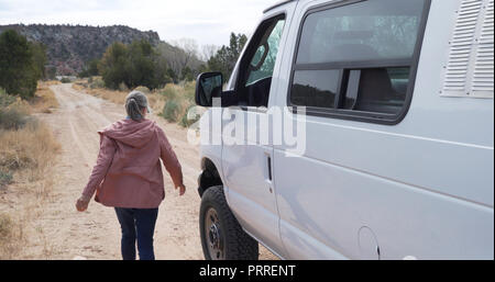 Candid senior woman in parked van stepping outside to walk away in natural park - Stock Photo