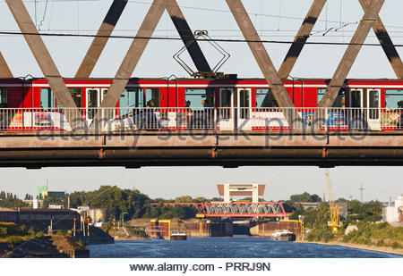 Duisburg Meiderich truss bridge with tram streetcar crossing Rhine-Herne-Canal waterway lock sluice gate tower water traffic transport inland port - Stock Photo