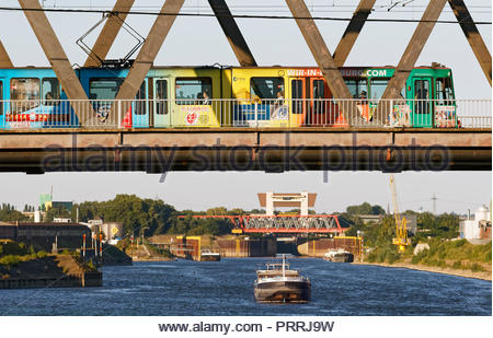 Duisburg Meiderich truss bridge tram streetcar crossing Rhine-Herne-Canal waterway cargo boat lock sluice gate tower water transport inland port - Stock Photo