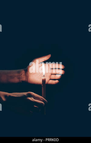 cropped view of person holding flaming candle in hands isolated on black - Stock Photo