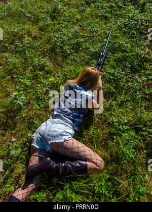 Faked Army young woman soldier with rifle in hand lying on stomach on grass-field aiming at something view from above nobody - Stock Photo