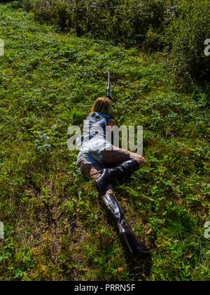 Faked Army young woman soldier with rifle in hand lying on stomach on grass-field aiming at something view from above - Stock Photo