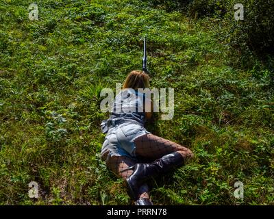 Faked Army young woman soldier with rifle in hand lying on stomach on grass-field aiming at something view from above rear back behind photographed - Stock Photo