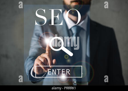 cropped view of professional developer touching SEO search - Stock Photo