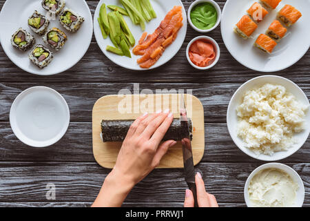 cropped shot of person holding knife and cutting delicious sushi roll - Stock Photo