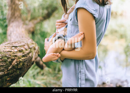 cropped view of mother holding little baby on hands - Stock Photo