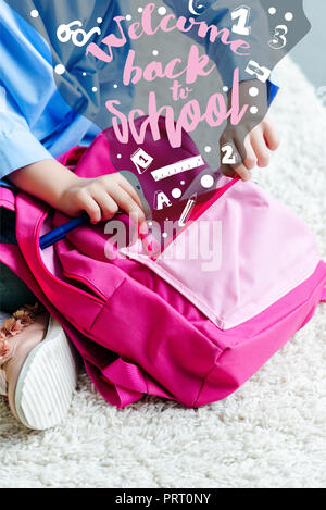cropped shot of child packing pink school bag at home, welcome back to school - Stock Photo