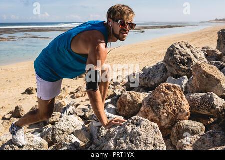 athletic man with armband climbing on rocks on beach, Bali, Indonesia - Stock Photo