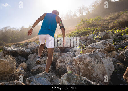 back view of athletic man climbing on rocks on mountain with back light - Stock Photo