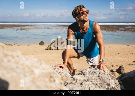 sportsman looking up while climbing on rocks on beach, Bali, Indonesia - Stock Photo