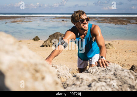smiling sportsman climbing on rocks on beach, Bali, Indonesia - Stock Photo