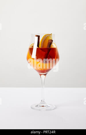 close up view of tasty mulled wine with orange pieces on white tabletop on grey background - Stock Photo