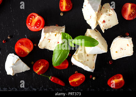 Pieces of camembert cheese with cherry tomatoes and basil leaves on a dark slate - Stock Photo