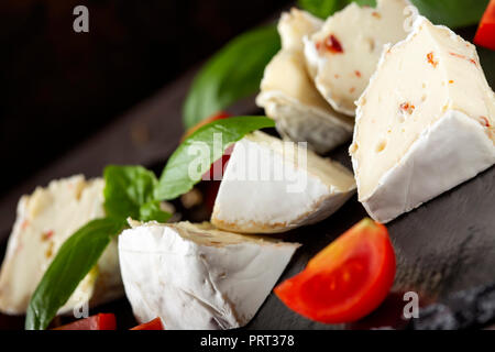 Pieces of camembert cheese with cherry tomatoes and basil leaves on a dark slate - close up view - Stock Photo