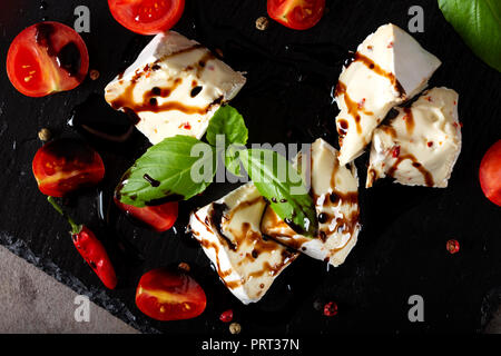 Pieces of camembert cheese with cherry tomatoes balsamic vinegar on a dark slate - top view - Stock Photo