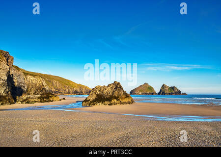 Rocks on Holywell Beach, with a view through  of the off shore Carters Rocks, Cornwall, UK - Stock Photo