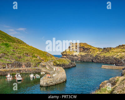 2 July 2018: Boscastle, Cornwall, UK - A couple admire the view of the harbour and its stunning rock formations from the breakwater. - Stock Photo