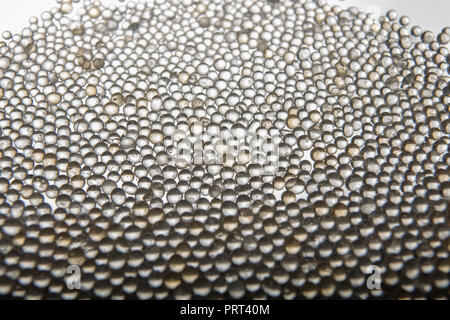 Macro of silica gel balls laying on white background.Its use to prevent mold, mildew, corrosion, odours and other moisture damage - Stock Photo