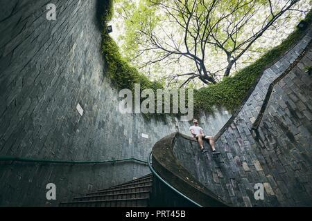 Lonely man sitting on the spiral staircase from underground walkway in Singapore. - Stock Photo