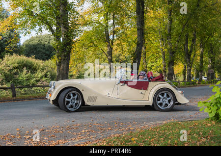 Morgan Aero Supersports car, a cream targo top semi convertible car with 2 passengers and the top down, on a country road in the UK. - Stock Photo