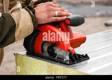 A young man welder in a working overall and working gloves grinds a sandwich panels  with a angle  grinder in the constraction side - Stock Photo