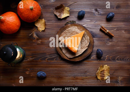 Pumpkin cheesecake, cooked at home, pumpkin, plum, vanilla , foliage on a wooden dark table. Autumn and winter cozy concept. Menu and restaurant conce