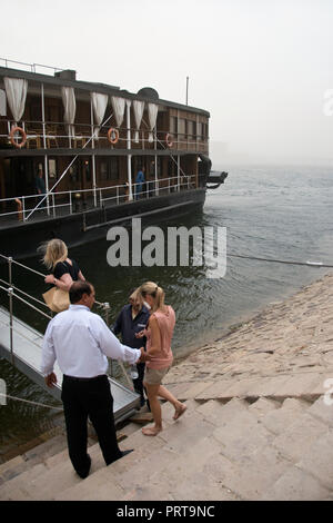 Tourists board the antique steamship MS Sudan during a sandstorm, while moored in the Nile at Qena, Egypt. - Stock Photo