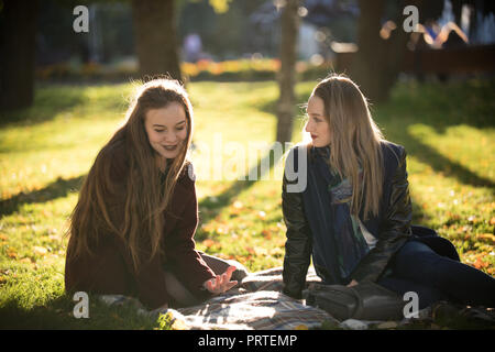 9c1c3efcd Two pretty girls in coats are walking in the autumn sunny park Stock ...