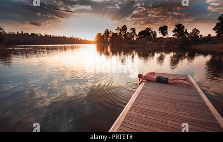 Young man without shirt lying face down on wooden jetty wetting his head in lake water - Stock Photo